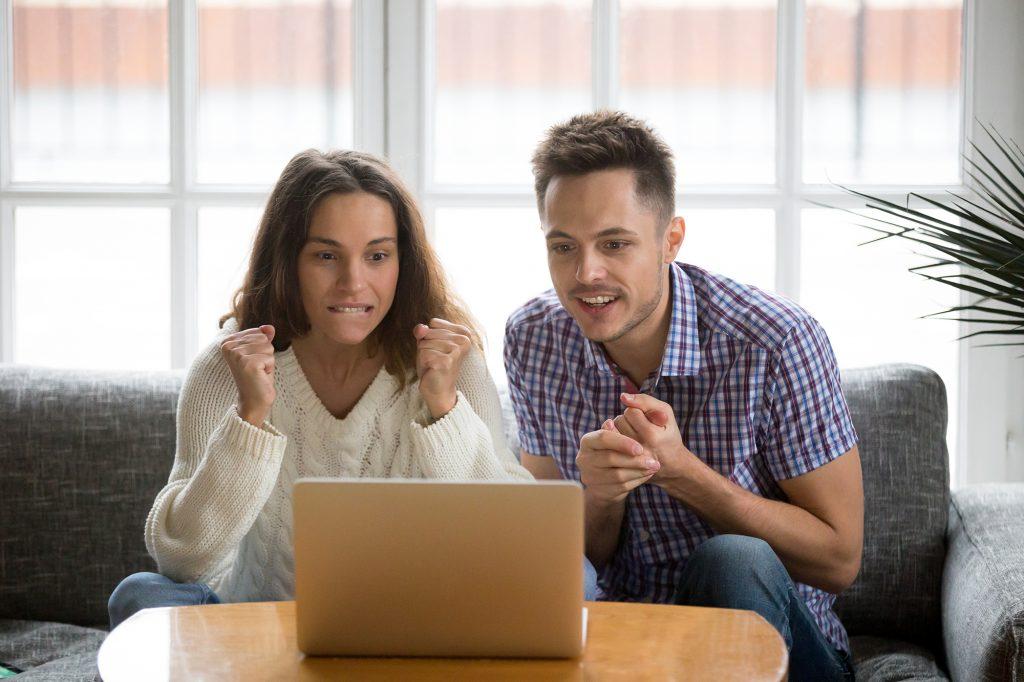 Молодые люди с интересом смотрят на экран ноутбука